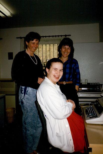 Christine lächelt, sitzt am Schreibtisch vor  einer Schreibmaschine hinter ihr stehen zwei lächelnde Gemeinde Mitarbeiterinnen.