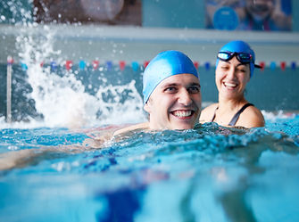 Female Swimming Teacher Giving Man One To One Lesson In Pool.jpg