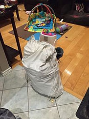 Cloth diaper bag filled with diapers in the living room surrounded by baby play toys