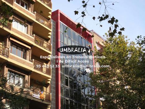 > Neteja de vidres a façana amb treballs verticals