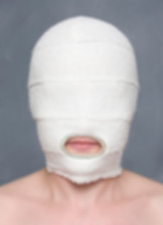 mask (cosmetic series) - a hood made from bandages with a cut out sterling silver hole revealing the mouth, representing the healing process associated with cosmetic surgery