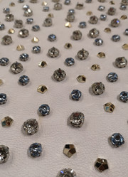 Borchie e pietre castonate montate su pelle  Studs and crystal stones with metal base applied on leather