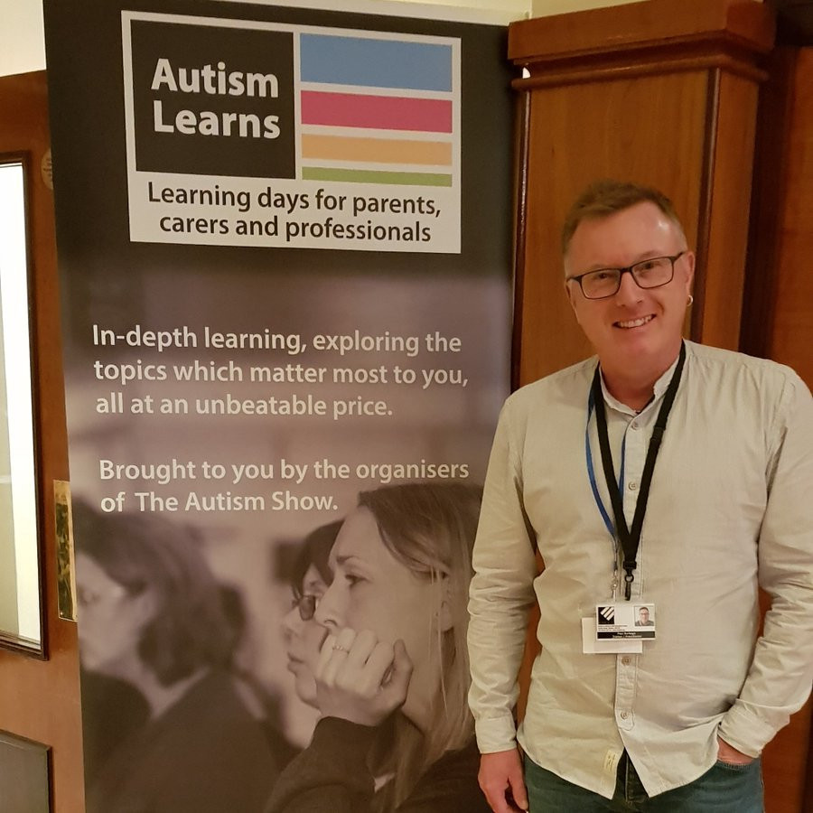 Studio 3 Trainer Paul Burbage standing in front of Autism Learns Conference Banner, 2019