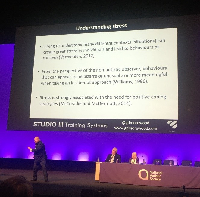 Gareth D Morewood on stage at NAS Professionals Conference, Birmingham, February 2020 in front of powerpoint presentation on Understanding Stress