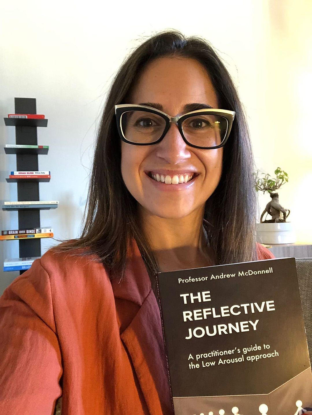 Sophia Algeria holding a copy of 'The Reflective Journey' by Professor Andrew McDonnell