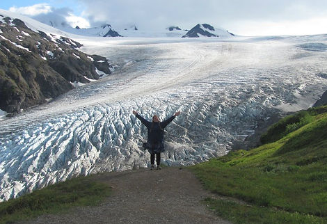 Rain standing in front of Harding Ice Field with arms raised