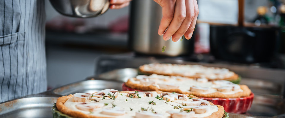 hand-of-cook-adding-herbs-and-cooking-pi
