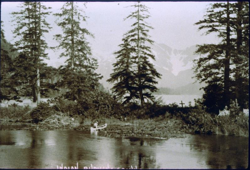 The Eyak Lake Spit, with visible grave-houses and crosses, looking north with Queen's Chair in the background. From Eyak Legends, Stories, and Photographs by John Johnson.