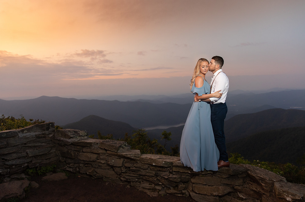A couple kissing cliffside during a sunrise at Craggy Gardens