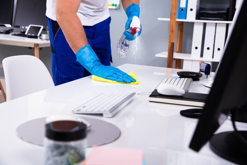Janitor cleaning white desk in modern of