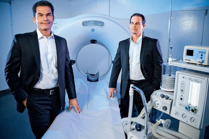 Homens na frente de um aparelho de tomografia