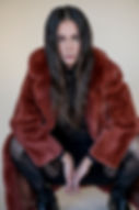 Model wearing rust colored fur jacket