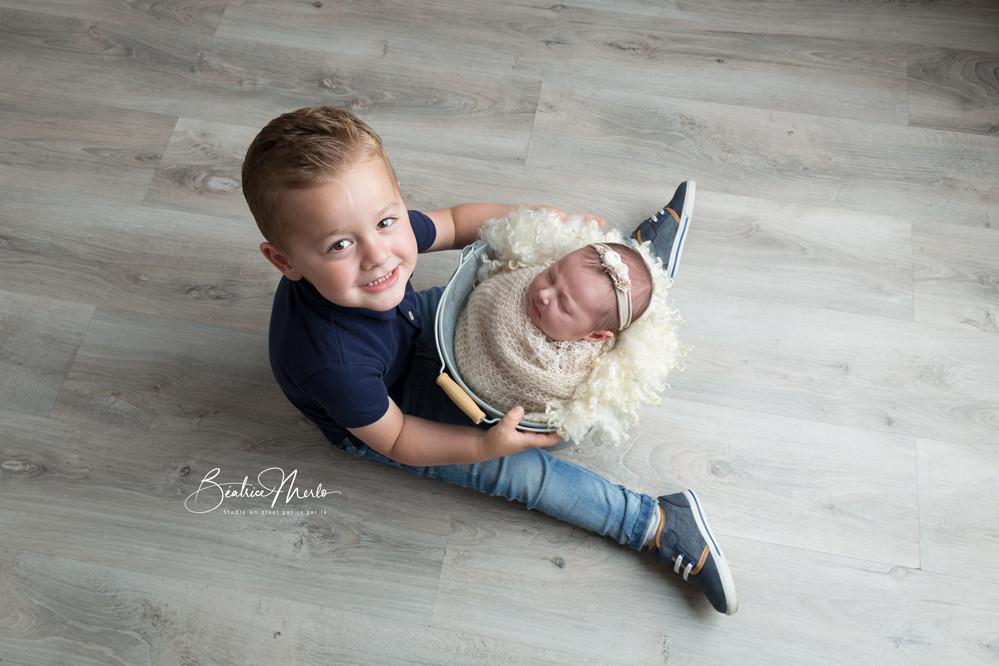 grand frère et petit bébé seau emmaillotement séance photo naissance