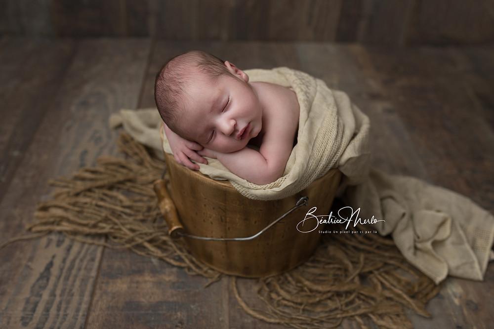bébé endormi dans seau bois