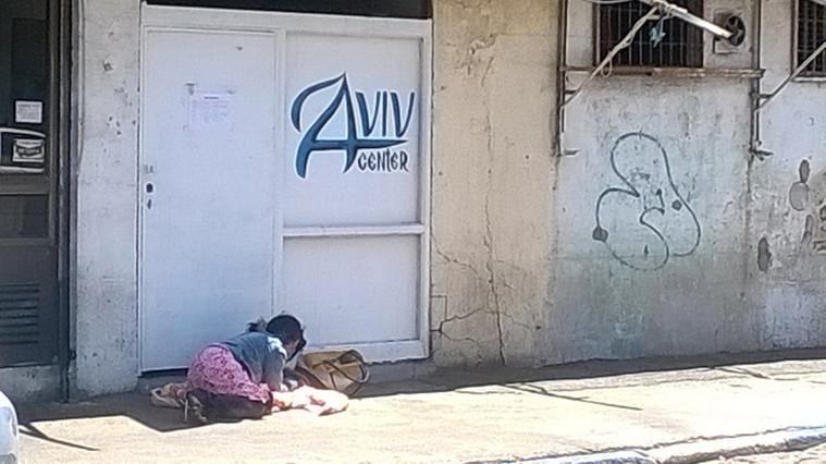 A street addict beside the doors of Aviv