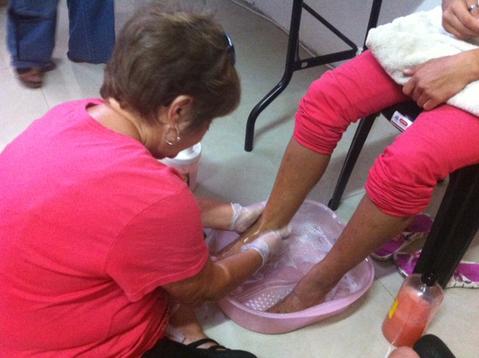 Mitarbeiterinnen waschen die Füße von obdachlosen Frauen