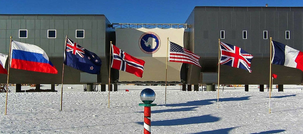 Flags of the original Antarctic Treaty signatories fly next to the ceremonial South Pole.