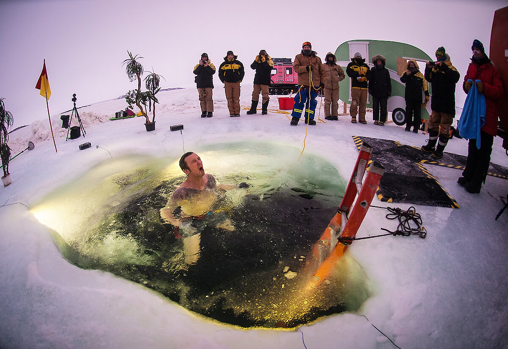 A shirtless man emerges from water which is surrounded by ice. Several people look on.