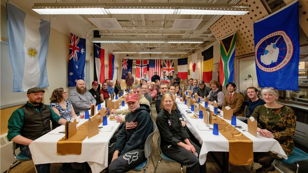 Dozens of people sit at long tables set with menus, glasses, and tableware. They are surrounded by several national flags.