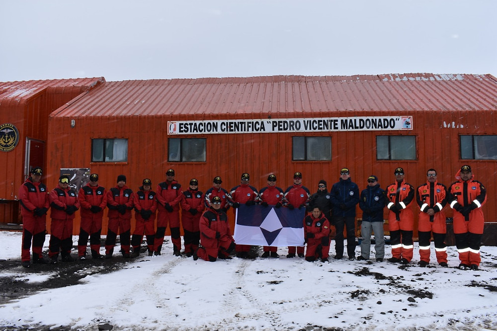 Members of the Ecuadorian and Chilean national Antarctic program stand with True South in front of Maldonado Base