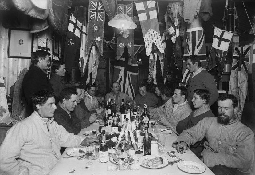 Men sit eating at a table surrounded by flags.