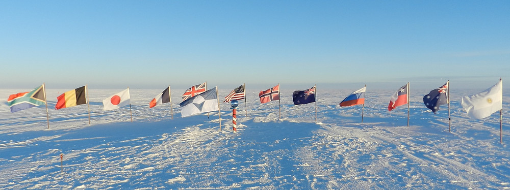 True South and the flags of the original 12 Antarctic Treaty signatories at the ceremonial South Pole