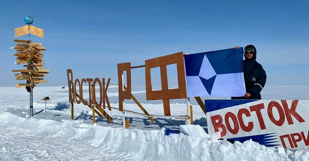 A member of the Russian national Antarctic program holds True South next to the Vostok station sign. Credit: Alexey Golubev