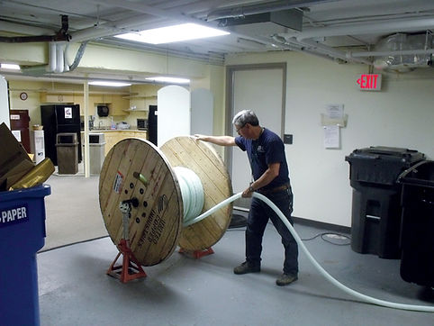 Photo of our technician unrolling a large spool of conduit