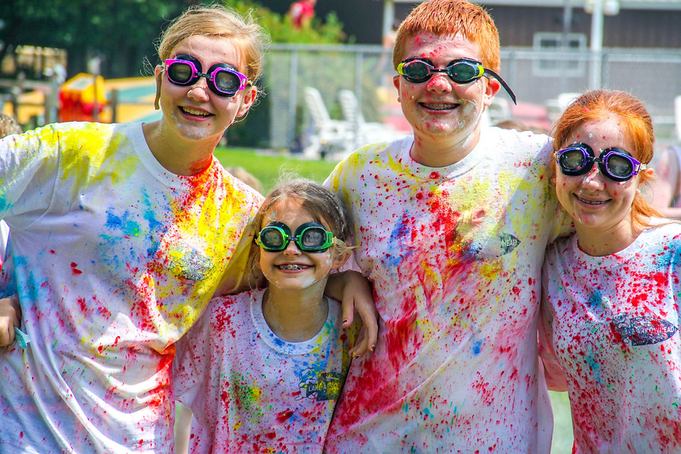 A group of teenagers splashed with color wearing goggles