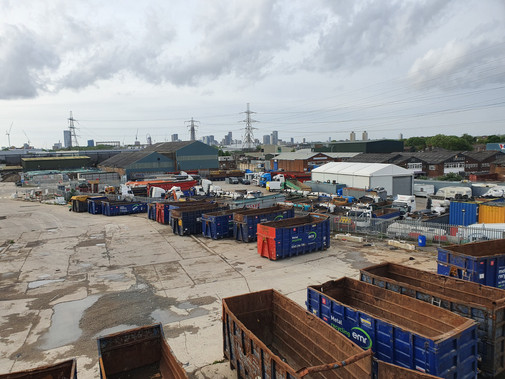 The east of the site is a metal scrapyard, characterised by the blue skips that line the east of the site