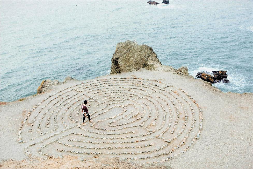 Yoga instructor walking in meditation circle on beach.