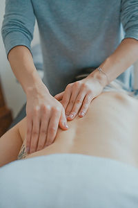 Massage therapist applying pressure with both hands to client's upper back