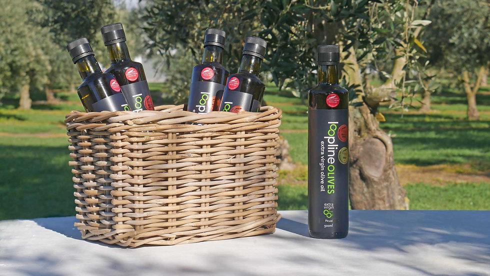 Bottles of Loopline Olives EVOO in a basket at the Olive Gove