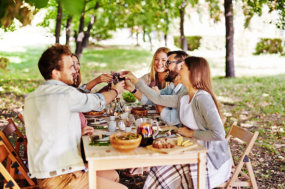 Group of young friends toasting with red wine at Thanksgiving table.jpg