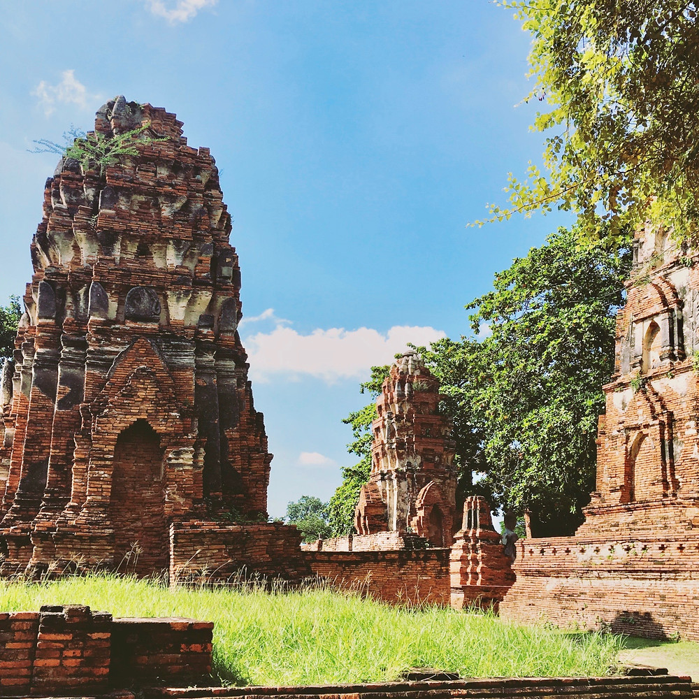 Red-brick temple ruins of Wat Mahathat under a bright, blue sky and greenery in the ancient city of Ayutthaya, Thailand