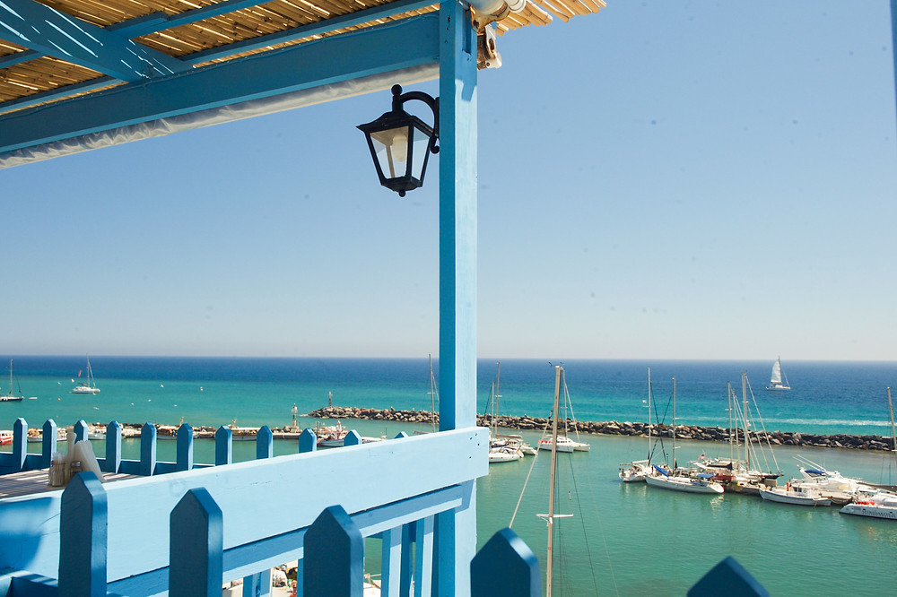 The patio of a restaurant overlooking Vlichada village's turquoise-water marina in Santorini, Greece