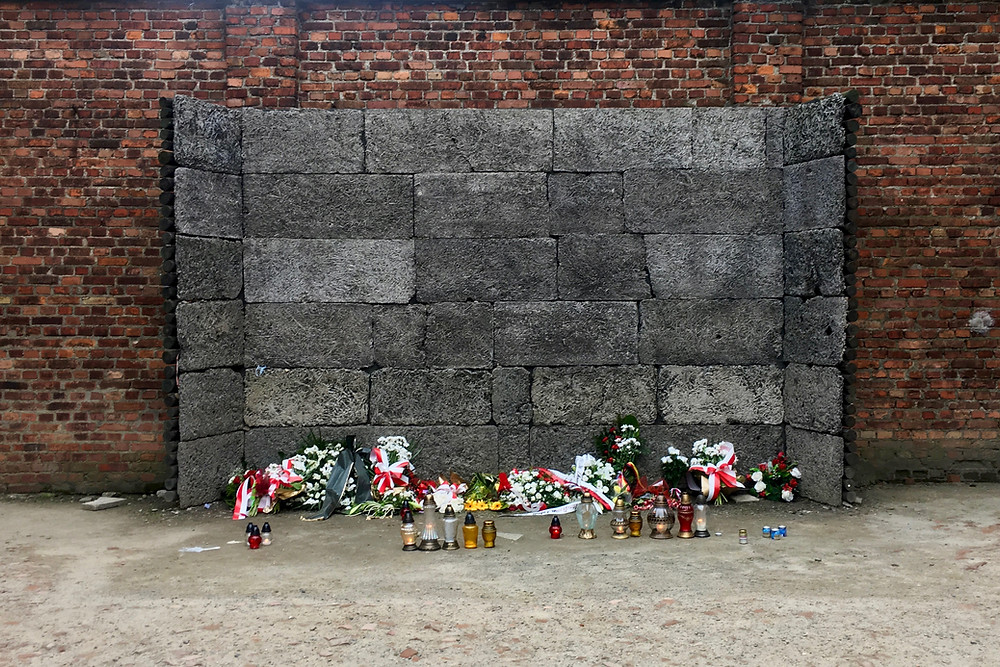 Flowers, wreaths, and candles on the ground in front of a grey stone section of the Death Wall at Auschwitz, Poland