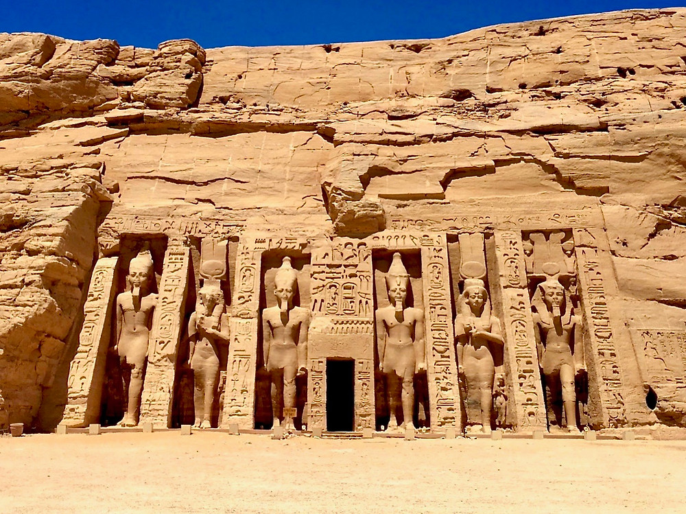 A view of the second Abu Simbel temple carved into the cliff with three statues and hieroglyphics on either side of its doorway