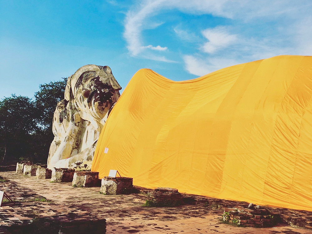 A stone reclining Buddha in a bright orange covering under sunny skies at Wat Lokaya Sutha in the ancient city of Ayutthaya