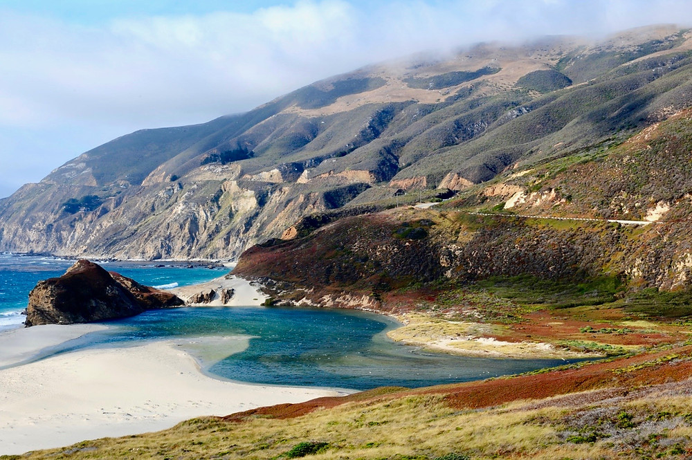 Multi-color rolling hills by the ocean with rocky shores and sandy beaches by the Pacific Coast Highway, California