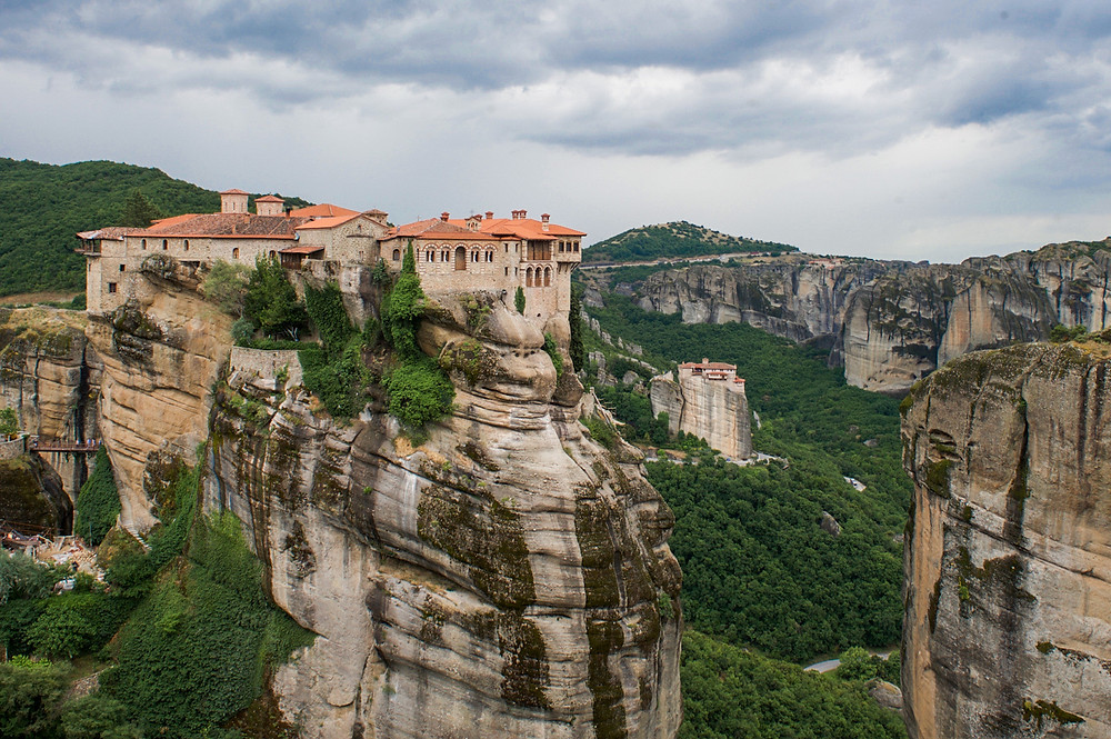 An orange-roofed monastery atop a rock column in Meteora, Greece with another monastery on a rock pillar in the background
