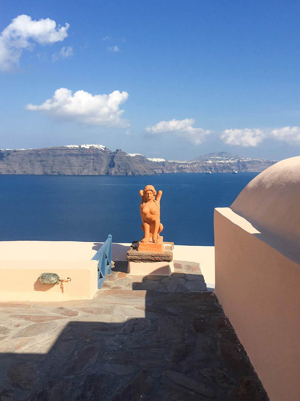 An orange seated sphinx statue in front of a deep blue sea and the cliffs of Santorini island on the other side