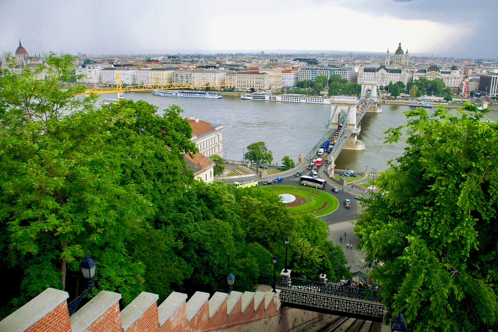 The view over the Danube River from the Castle Hill Funicular Tram track where landmarks including the Hungarian Parliament Building, Széchenyi Chain Bridge, and St Stephen's Basilica can be seen among the cityscape in the distance