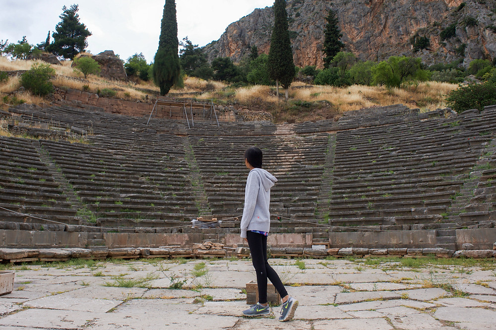 Eryn stands in front of an ancient amphitheater