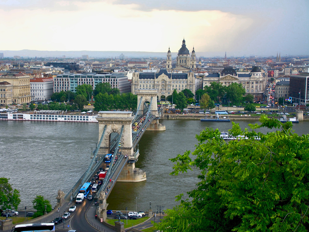An elevated view of the Széchenyi Chain Bridge crossing the Danube River from Buda to Pest before the Pest city skyline in Budapest, Hungary