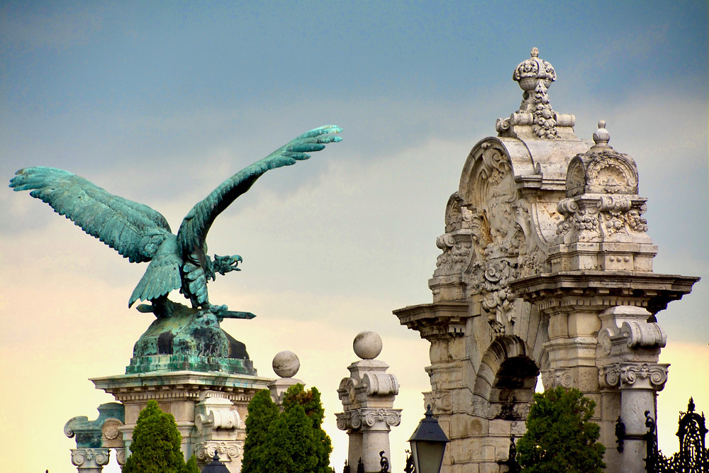 The turquoise bronze statue of the mythological Turul falcon on Castle Hill, Budapest before a gradient blue-yellow sky