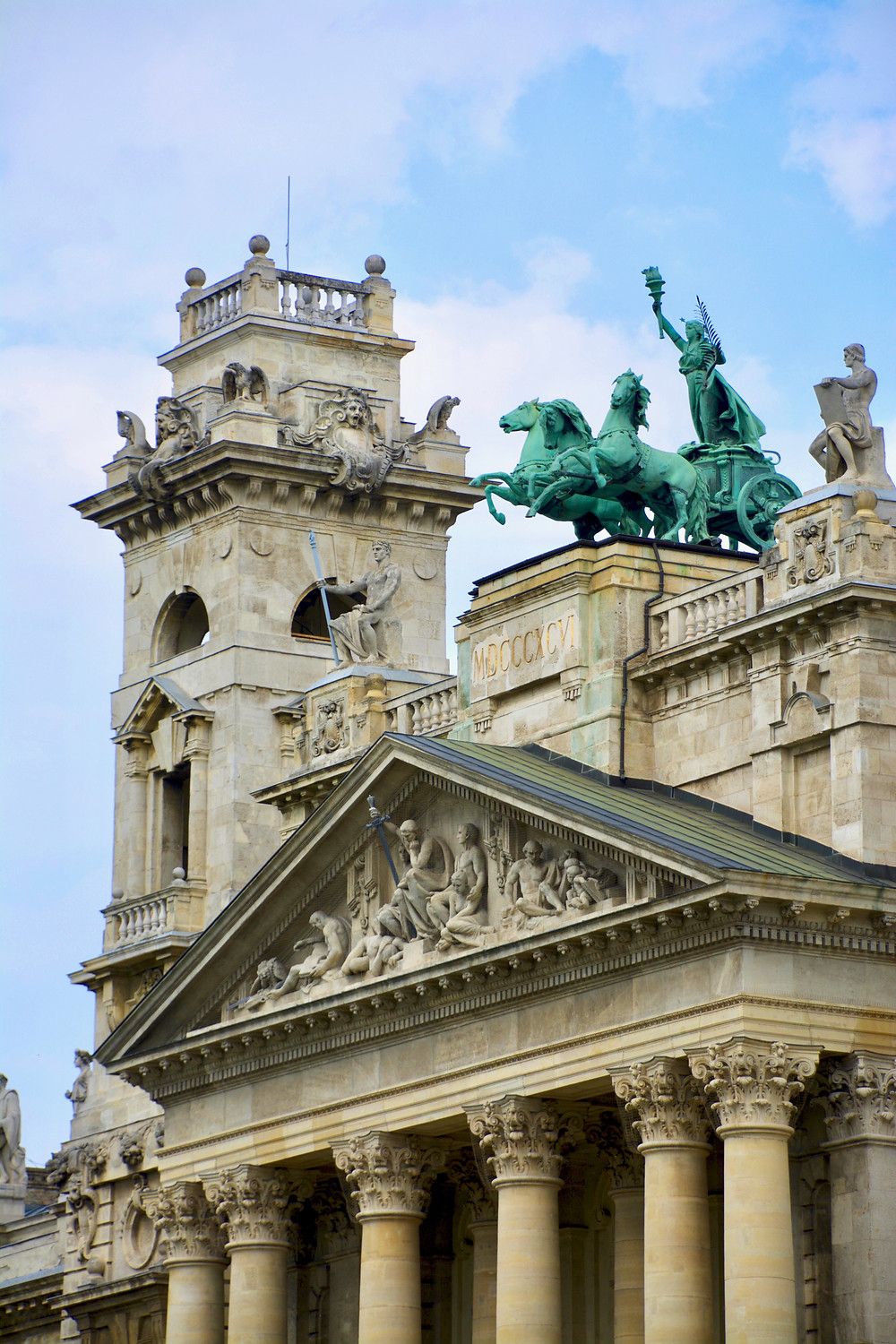 A closeup of the detailed facade of the Hungarian National Museum of Ethnography lined with carved stone horse and human figures in Budapest