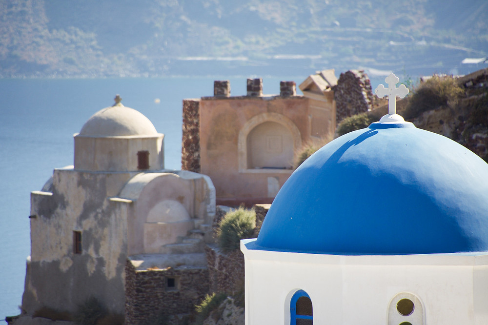 A whitewashed, blue-domed church building topped with a white cross in front of the an old brown structure on a cliffside in Oia, Santorini, Greece