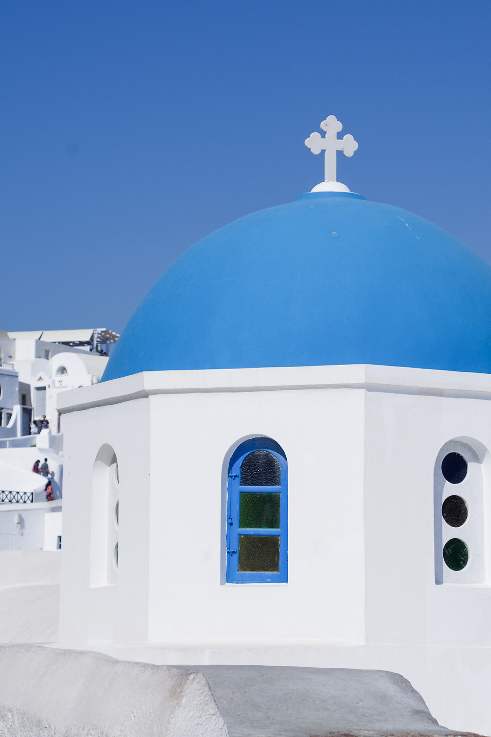 A whitewashed church building with a blue-domed roof and a white cross at the top in Oia, Santorini, Greece