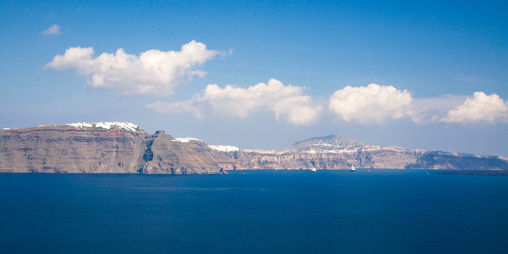 The cliff landscape of Santorini island stretched across the horizon amid a deep blue ocean and a partially cloudy sky